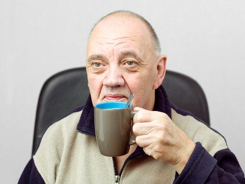 portrait vieil homme pause café sur fond gris