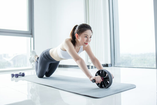Fit woman doing workout and exercise with roller wheel,Individual balance sport