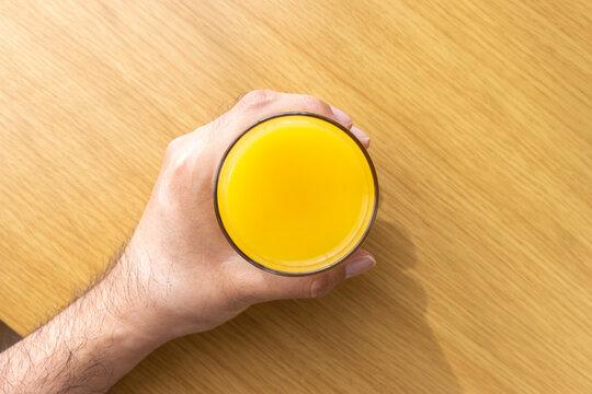 オレンジジュースの入ったグラスを持つ男の手