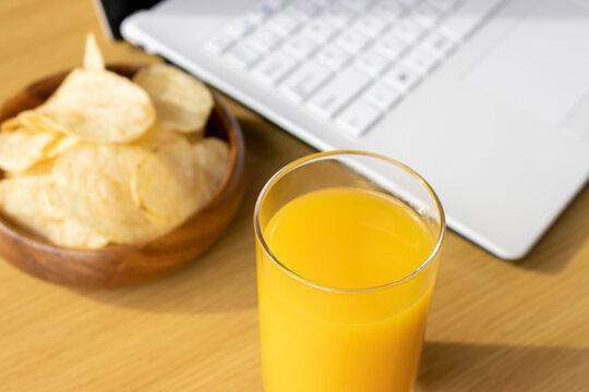 休憩時間におやつを食べ、ノートパソコンを使うイメージ