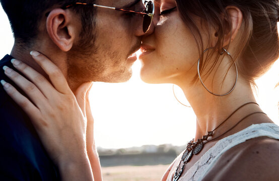 Close-up of young romantic couple is kissing and enjoying the company of each other outdoor at sunset
