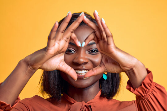 Smiling young african american woman showing shape heart with hands heart-shape sign posing isolated on yellow background in studio. People lifestyle concept. Close up view.