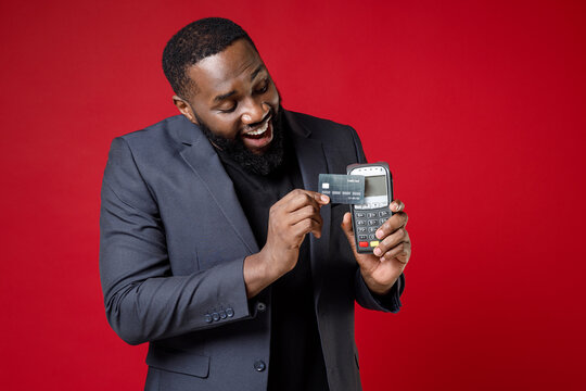 Cheerful young african american business man 20s in classic jacket suit hold wireless modern bank payment terminal to process acquire credit card payments isolated on red background studio portrait.