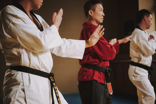 People practice karate techniques in the gym.