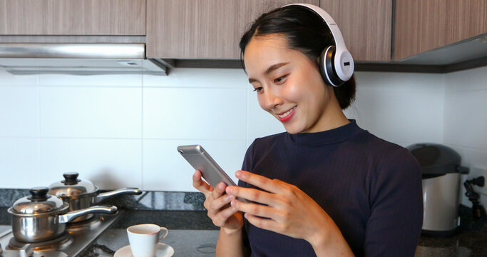 Asian women wearing headphone and listening to music in the kitchen at home