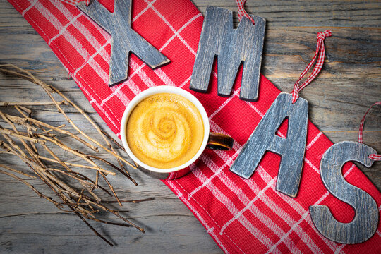 Cup of creamy coffee and wooden letters XMAS on a red kitchen towel. View from above.