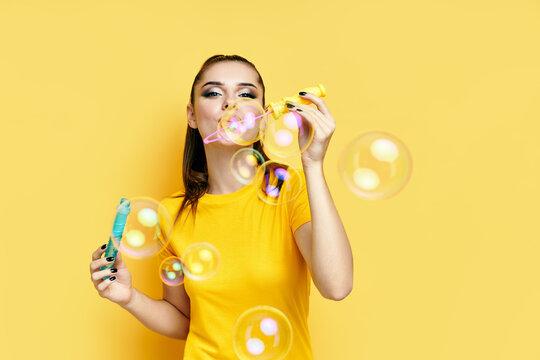 Happy beautiful woman blowing soap bubbles