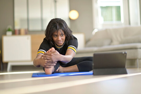 African-american woman doing virtual fitness exercices, digital class on tablet