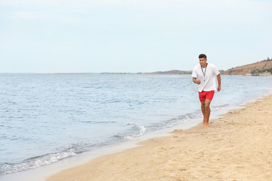 Handsome male lifeguard running on sandy beach