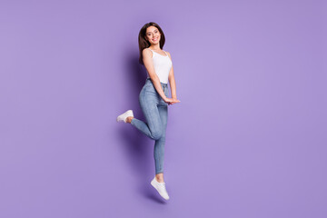 Full length photo of happy charming brown haired girl jump up enjoy weekend isolated on purple color background Wall mural