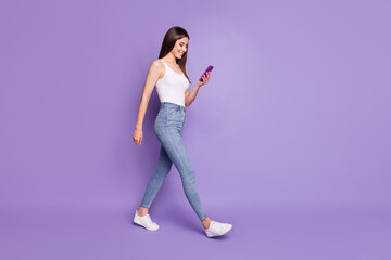 Full size profle side photo of happy brown haired girl text walk hold phone wear white tank-top isolated on purple color background Wall mural