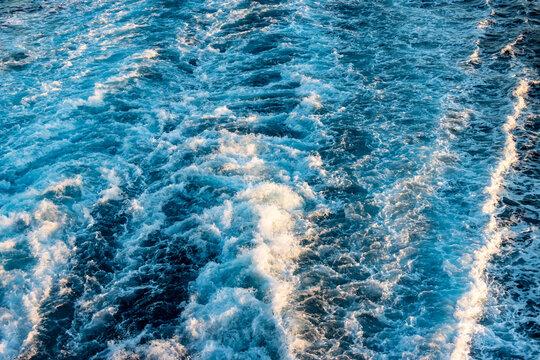 Sprudelndes Wasser mit Wellen hinter der Schiffsschraube im Mittelmeer im Morgenlicht