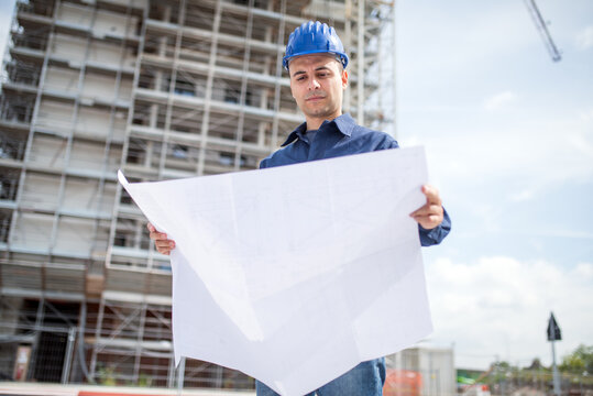 Site manager reading a blueprint in front of a construction site
