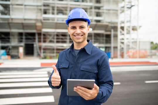 Worker using his tablet in front of a construction site