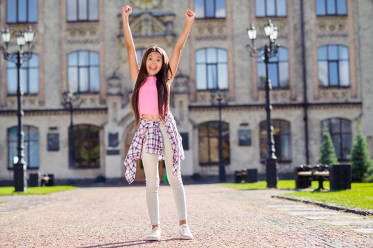 Photo of excited schoolgirl raise two hands open mouth wear pink top white trousers urban city outside