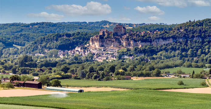 Panoramic view of the medieval castle Beynac, rising on a cliff above the River Dordogne in the village of Beynac-et-Cazenac. Agricultural fields in the foreground. Dordogne, Aquitaine, France.