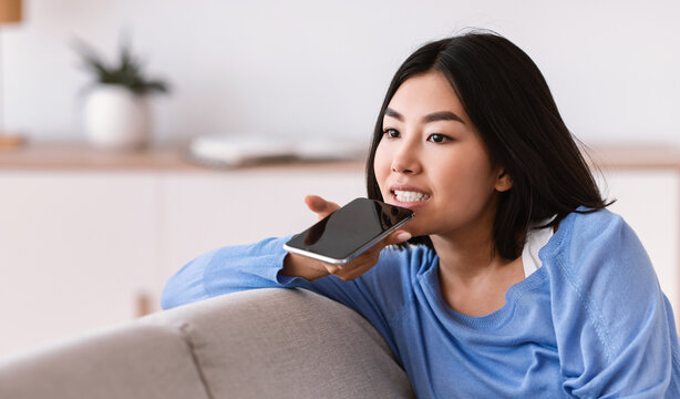 Young asian woman using voice assistant on smartphone