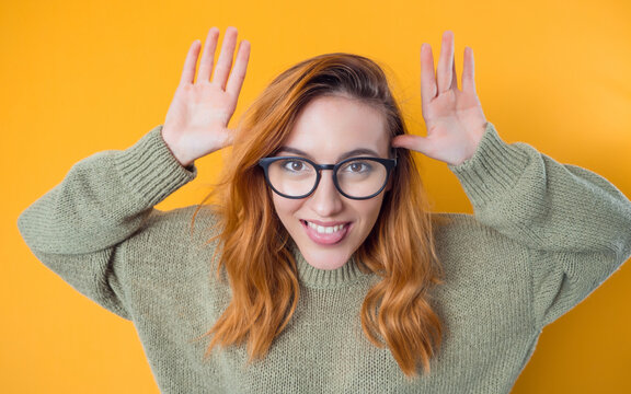 Young woman sticking tongue out, isolated on yellow background. Joke concept. Silly girl