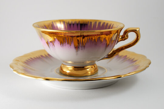empty porcelain tea cup with gilding on a white backdrop