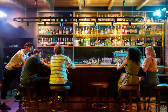 Rear view of three guys drinking beer, looking at women, two girlfriends sitting at the bar counter. Friends spending time at night club, restaurant
