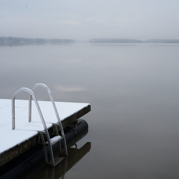 wooden pier and ladder on the lake covered with snow