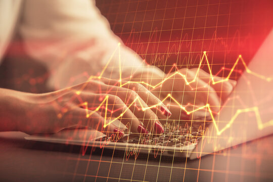 Double exposure of businesswoman hands typing on computer and forex chart hologram drawing. Financial analysis concept.