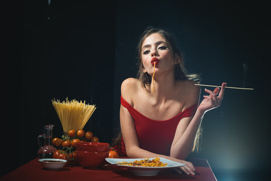 Young sexy woman eating tasty pasta on black.