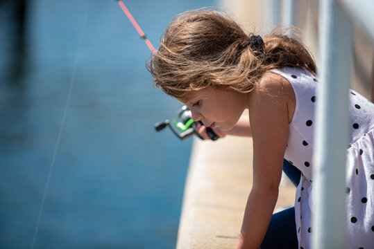 Fishing, lovely girl child fishing on the pier on sea.