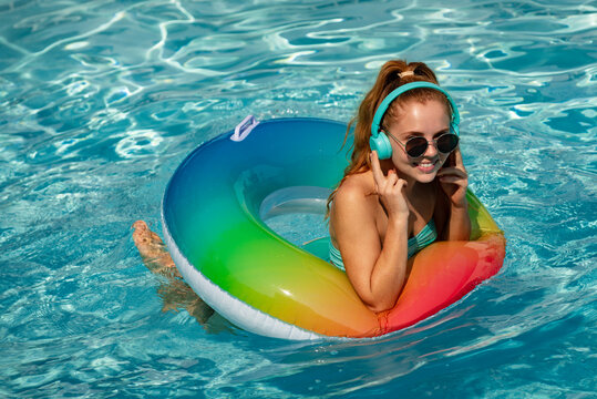 Summer music. Gorgeous young woman posing in bikini near pool, listen to music. Summer Vacation. Enjoying Woman in bikini in the swimming pool with headphones.