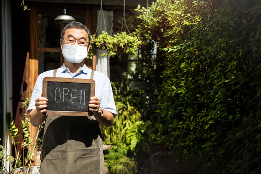 Japanese shop owner in face mask new normal post covid 19