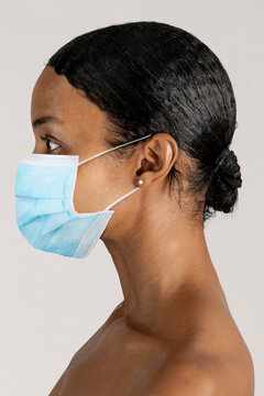 Black woman wearing a surgical mask in a profile shot