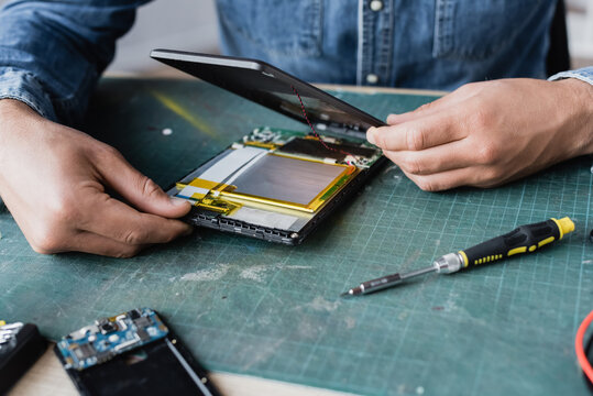 Close up view of repairman hands disassembling broken digital tablet near screwdriver at workplace
