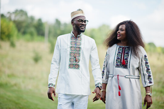 African couple in traditional clothes at park.