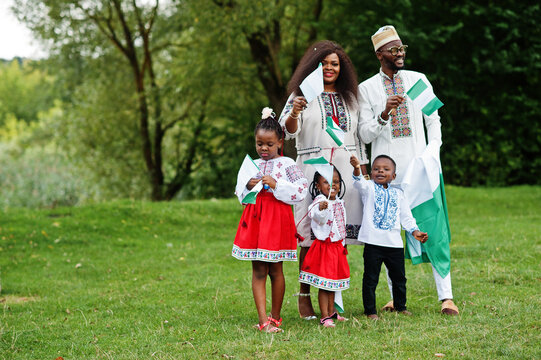 African family in traditional clothes with nigerian flags at park.