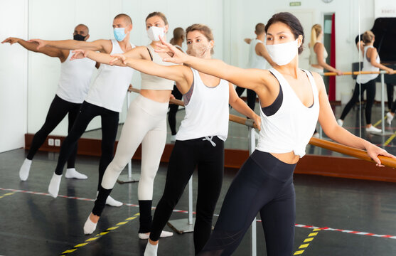 Group of people in masks doing exercises using barre in gym during coronavirus .pneumonia outbreak