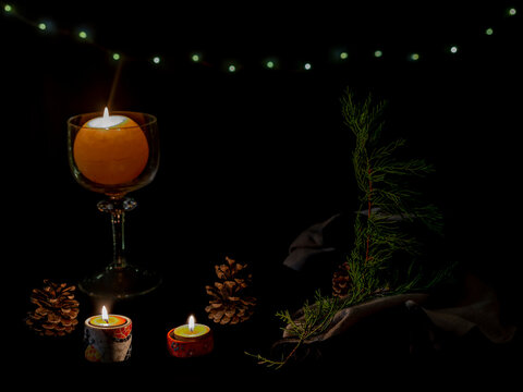 Christmas composition with burning candles, conifer branches, pine cones and fairy lights on a dark background