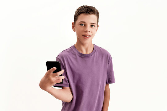 Teenaged disabled boy with cerebral palsy looking at camera and holding smartphone, posing isolated over white background