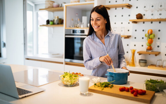 Happy beautiful woman learning to cook with online course at home