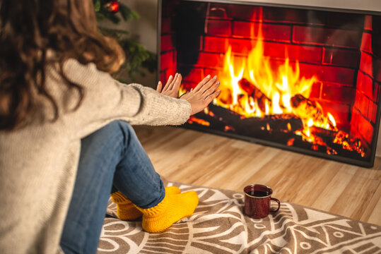 Girl in a sweater and socks is sitting next to the fireplace, which is depicted on the TV screen and warming her hands