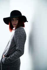 Mysterious fashion young woman with black hat, indoor portrait