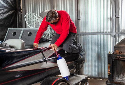 A man checks and maintains a motor boat
