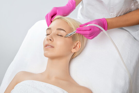 Beautiful girl with clean fresh skin.Cosmetologist makes  procedure microdermabrasion on the face against acne and blackheads near the eyes. Women's cosmetology in the beauty salon.