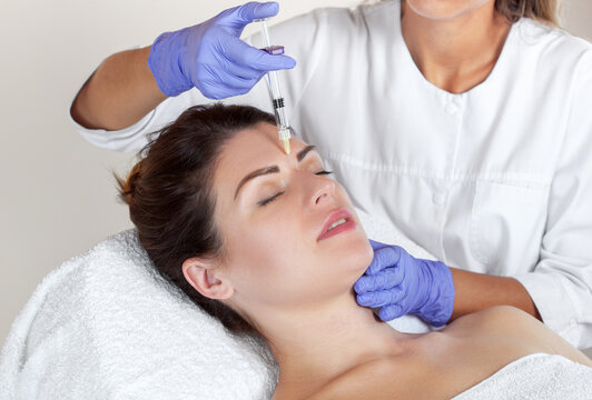 Cosmetologist makes rejuvenating anti wrinkle injections on the face of a beautiful brunette woman. Female aesthetic cosmetology in a beauty salon.