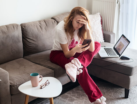 Young bored woman sitting on sofa and  browsing social media on smartphone