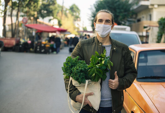 Millennial man with cloth face mask standing outdoor with reusable bag with vegetables inside and street local farmers market behind him