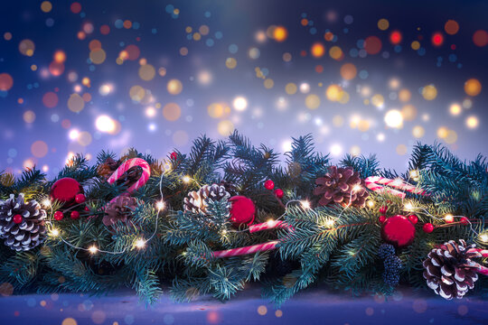 Decorated and illuminated Christmas garland with fir branches against a blurred lights background at night.