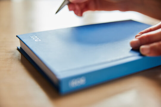 Close Up Of Woman Opening New Year 2021 Diary On Table At Home