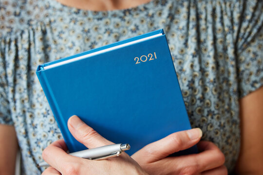 Close Up Of Woman Holding New Year 2021 Diary At Home