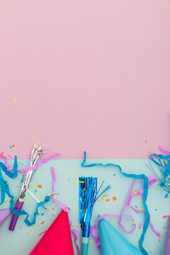 Party hat, party blowers and confetti on pink and blue background