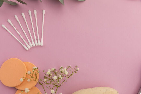 Cotton buds and cotton pads and plants on pink background